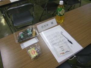 席札、名札、資料、筆記用具と、経理部長の心遣い、おにぎり、お手拭き、お菓子。